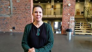 Ann-Kristin Stenkull-Aura framför en tegelvägg.