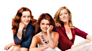 Kolme nuorta naista katsoo kameraan ja hymyilee. Studiokuva.