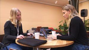 Amanda Rejström och Anna Eriksson sitter vid ett runt bord och arbetar vid bärbara datorer.