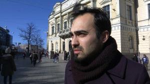 Ozan Yanar, riksdagsledamot för De gröna, står utanför Gamla studenthuset i Helsingfors.