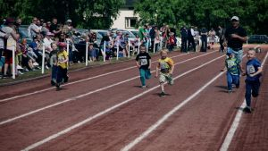 Pienet lapset juoksevat kilpaa Pylkönmäen urheilukentällä. Aikuiset katsovat kentän reunalla, mutta yksi mies juoksee pikkuisensa perässä kentällä.