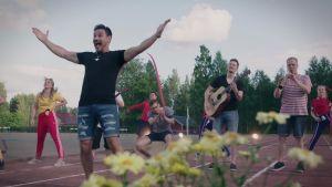 Tommi Soidinmäki, muusikot ja tanssijat esiintyvät rennosti pukeutuneina kesäisellä urheilukentällä.