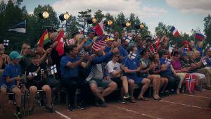 Muutamakymmentä ihmistä istuvat urheilukentän vierellä penkillä ja heiluttavat lippuja.