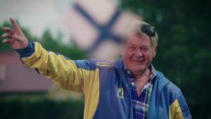 Sinikeltaiseen urheiluasuun pukeutunut 80-vuotias Pentti hymyilee ja tuulettaa kesäisessä maisemassa.