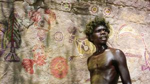 Nuori aboriginaali seisoo kalliomaalausten edessä. Kuva elokuvasta Walkabout.