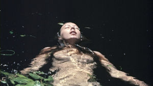 Nuori nainen kelluu alasti vedessä. Kuva elokuvasta Walkabout.