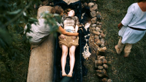 Nuori nainen jonkinlaisessa avoimessa arkussa kivireunusten ympärillä. Toinen nainen asettelee hänen käsiään.