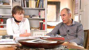 Susanne Gottberg ja Jörn Donner istuvat pöydän äärellä ja katsovat toisiaan.