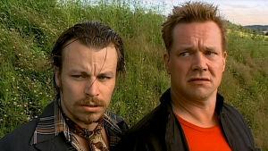 Kaksi miestä seisoo taustalla nurmikkoa.