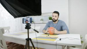 Mies istuu pallo  kädessä pöydän ääressä ja puhuu videokameralle.