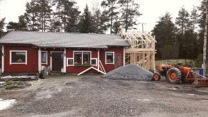 Ett rött 1980-tals hus med vita knutar, intill en hög med grus och man ser att stommen till en tillbyggnad är på gång.