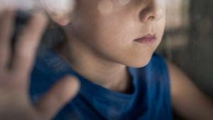 Närbild av barn som står vid fönster. Han bär en blå skjorta.