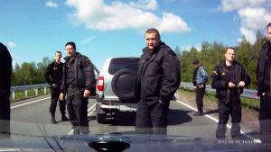 Univormuihin pukeutuneita miehiä auton edessä tuijottaa tuulilasin läpi.