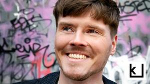 Eino Nurmisto hymyilee graffitiseinän edustalla.