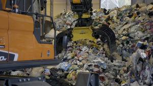 Kauhakuormaajan kauha ottaa muovia kasasta Riihimäen muovinjalostamolla.