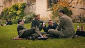 Tolkien och hans tre bästisar sittande på gräsmattan utanför en av universitetsbyggnaderna i Oxford.
