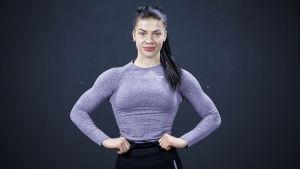 Fitness-urheilija Pernilla Böckerman poseeraa kameralle tummaa taustaa vasten.