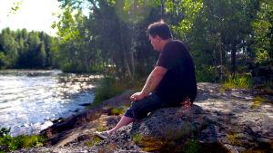 en man sitter på en sten vid stranden och tittar ut mot havet