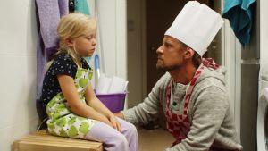 Pappan (Peter Kanerva) tröstar Vilda (Sofia Sittnikow) som mår illa.