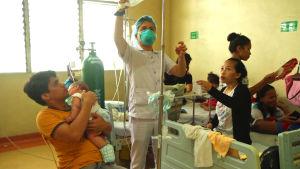 Sjukskötare på Filippinerna tar hand om mässlingspatienter.