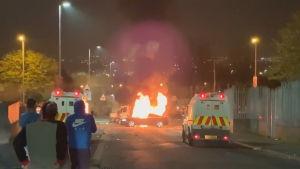 På bilden brinner en bil i londonderry. Tre åskådare syns i förgrunden.