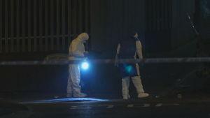 På bilden syns två tekniker utreda en brottsplats i Londonderry.