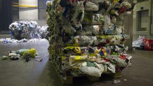 Muovijätepaaleja hallissa.