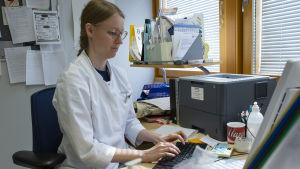 En kvinnlig läkare sitter vid ett skrivbord och skriver på en dator.