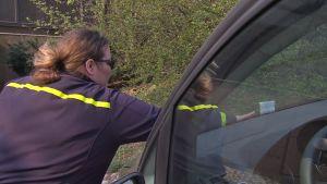 En parkeringskontrollant placerar en kontrollavgiftslapp på en felparkerad bil.
