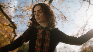 Edith Bratt (Lily Collins) dansar ute i naturen.