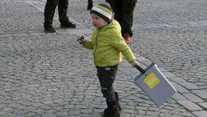 Lapsi kävelee Tampereen keskustorilla I love muovi -sangon kanssa.