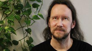 Kirjailija JP Koskinen istuu viherkasvin vieressä