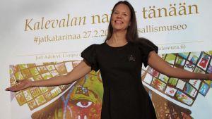 Kirjailija Tiina Piilola levittää käsiään kuten Kalevalan Aino Suomen Kansallismuseossa.