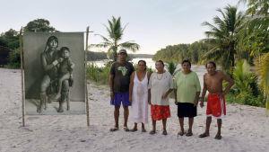 Viisi miestä ja naista seisoo hiekkarannalla vierellään mustavalkoinen kuva äidistä ja tyttärestä.