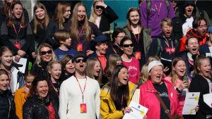 Ihmiset kannustavat iloisina Oulua voittoon leikkimielisessä I love muovi -kisassa.