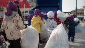 Lapset vievät muovijäteitä jäteautoon.