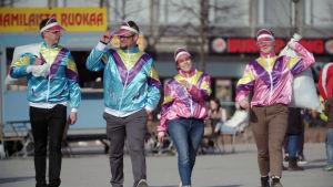 Neljä henkilöä kävelevät yhdessä rintamassa muovijätepussit mukanaan.