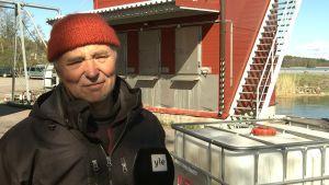 Fiskaren Olavi Sahlstén, en man med röd stickad mössa.