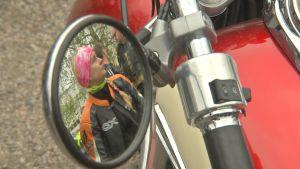 En motorcyklist med rosa buff syns i sidospegeln på en motorcykel.