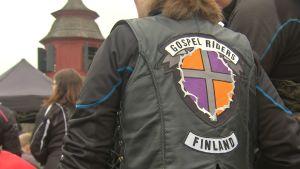"""En motorcyklist med texten """"Gospel Riders Finland"""" bak på sin läderrock står vid en kyrka."""