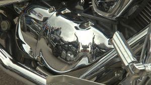 En motorcykel speglas i kromet på en annan motorcykel.