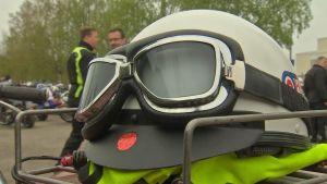 En vit, gammaldags motorcykelhjälm och äldre modell motorcykelglasögon ligger på en motorcykel.