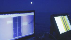 Scanners och ekolod i öppen båt på natten i månsken ute på havet.