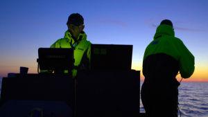 Två män på nattlig båtfärd letar med scanner efter det försvunna skeppet Irma.