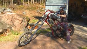 En man i långt skägg med glasögon sitter på en specialbyggd Choppermotorcykel.