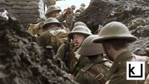 Valokuva ensimmäisen maailmansodan ajalta. Miehet kävelevät jonossa kapeassa juoksuhaudassa, yksi mies katsoo tupakka suussa kameraan. Peter Jacksonin dokumenttielokuvasta They shall not grow old.