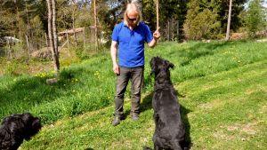 Björn Holmberg förmanar sin hund med fingret i luften, medan den andra hunden tittar på.