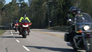 En konvoj motorcyklar längs en landsväg.