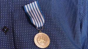 """Livräddningsmedaljen i närbild. En rund silvermedlaj med texten """"För räddning av människoliv"""" Medaljen har ett blåvitttt snöre."""