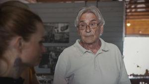 Vanhempi silmälasipäinen mieshenkilö vaaleassa pikeepaidassa